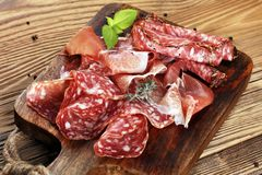 Food tray with delicious salami, raw ham and italian crudo or ja. Mon. Meat platter with selection Stock Photos