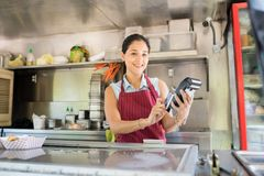 Food truck owner with credit card terminal. Beautiful Hispanic food truck worker receiving payment with a credit card and smiling stock images