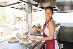 Food truck owner making hamburgers. Portrait of a beautiful young food truck owner making burgers and enjoying her work stock photography