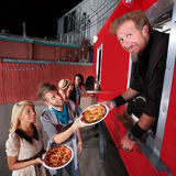 Pizza Dinner at Food Truck. Food truck owner serving pizza to happy couple stock images