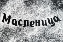 Food typography russian phrase «Maslenitsa» shrovetide spell. Ing with sugar powder. Lettering on dark background. Top view. Flat lay Stock Image