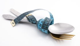Food under control. Cutlery with a measuring tape, diet, moderate eating Stock Images