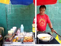 A food vendor cooks fish balls, sausages and quail eggs which he sells on a food cart Royalty Free Stock Photo