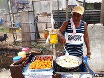 A food vendor cooks fish balls, sausages and quail eggs which he sells on a food cart Stock Photos