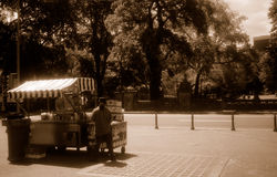 Food vendor in park. A food vendor selling snacks on in an open area of Central Park, New York. Sepia tone Stock Photo