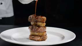Food video in slow motion. Chef pouring sauce on frilled steak. Restaurant meat dish serving. Grill smocked barbecue stock footage