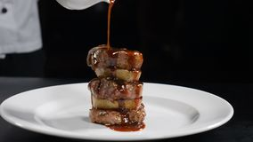 Food video in slow motion. Chef pouring sauce on frilled steak. Restaurant meat dish serving. Grill smocked barbecue stock video