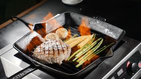 Food video in slow motion. Professional chef in blue gloves cooking with flame on frying pan pork, steak and vegetables. With alcohol stock video footage