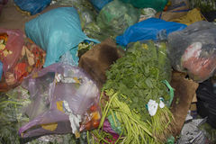 Food Wastage. Fruits and vegetables and plastic bags thrown away in garbage Stock Photo