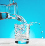 Water pouring into a glass on blue background Stock Photos