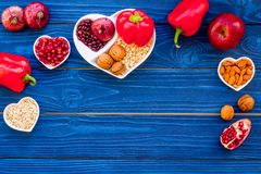 Food which help heart stay healthy. Vegetables, fruits, nuts in heart shaped bowl on blue wooden background top view.  Royalty Free Stock Photos