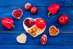 Food which help heart stay healthy. Vegetables, fruits, nuts in heart shaped bowl on blue wooden background top view.  stock photography
