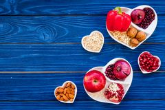 Food which help heart stay healthy. Vegetables, fruits, nuts in heart shaped bowl on blue wooden background top view.  Royalty Free Stock Images