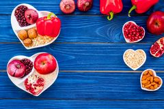Food which help heart stay healthy. Vegetables, fruits, nuts in heart shaped bowl on blue wooden background top view.  Royalty Free Stock Photography