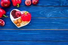 Food which help heart stay healthy. Vegetables, fruits, nuts in heart shaped bowl on blue wooden background top view.  Royalty Free Stock Image