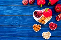 Food which help heart stay healthy. Vegetables, fruits, nuts in heart shaped bowl on blue wooden background top view.  Stock Photo