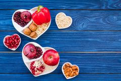 Food which help heart stay healthy. Vegetables, fruits, nuts in heart shaped bowl on blue wooden background top view.  Stock Image