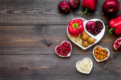 Food which help heart stay healthy. Vegetables, fruits, nuts in heart shaped bowl on dark wooden background top view.  Stock Photos