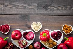 Food which help heart stay healthy. Vegetables, fruits, nuts in heart shaped bowl on dark wooden background top view.  Royalty Free Stock Image