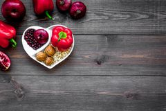 Food which help heart stay healthy. Vegetables, fruits, nuts in heart shaped bowl on dark wooden background top view.  Royalty Free Stock Photography