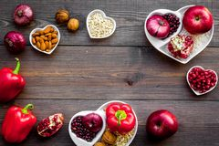 Food which help heart stay healthy. Vegetables, fruits, nuts in heart shaped bowl on dark wooden background top view.  Stock Photo