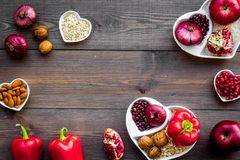 Food which help heart stay healthy. Vegetables, fruits, nuts in heart shaped bowl on dark wooden background top view.  Stock Image
