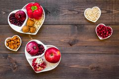 Food which help heart stay healthy. Vegetables, fruits, nuts in heart shaped bowl on dark wooden background top view.  Royalty Free Stock Images