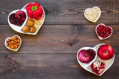 Food which help heart stay healthy. Vegetables, fruits, nuts in heart shaped bowl on dark wooden background top view.  Royalty Free Stock Photos