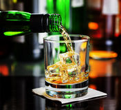 Whiskey pouring a glass in a bar Stock Photography