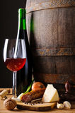 Food and wine. Stille life with traditional food, red wine and wooden barrel Stock Images
