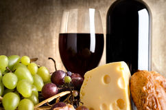 Food and wine. Wine, cheese, grapes and sausage on an old canvas Royalty Free Stock Images