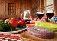 Food and wine on table. Wine, sausage and vegetables on table, traditional Bulgarian table setup with fresh food and glasses of red wine Stock Images