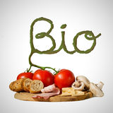 Food on wooden board isolated on white with stem shaped inscription bio Stock Photo