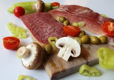 Food - wooden cutting board with slices of salami and ham, olives, mushrooms and cut tomatoes and green peppers Royalty Free Stock Photography