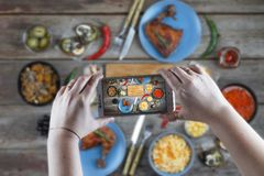 Food, taking pictures, eating out, eating in a cafe, technology,. Food. A young woman is taking pictures a dining table with a smartphone for instagrams. Concept royalty free stock photo