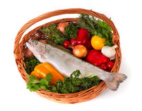 Foodbasket with fresh trout. Still life. Basket with fresh vegetables and trout Stock Images