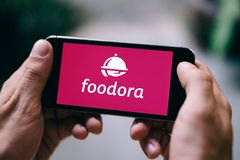 BERLIN, GERMANY - APRIL 14, 2018: Closeup of iPhone screen with FOODORA APP LOGO and ICON. Foodora is a popular food delivery platform that uses bicycles for Stock Images