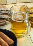 Foods and beer mug. Beer mug sausages, pretzels and grilled fishes on wooden table Stock Image