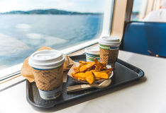 Foods and coffee in cafeteria near by big window with view of the island in the back ground,in ferry. Royalty Free Stock Photography