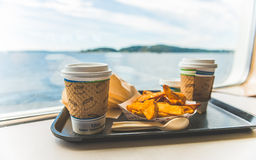 Foods and coffee in cafeteria near by big window with view of the island in the back ground,in ferry. Stock Photo