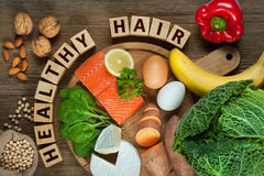 Foods for healthy hair. Healthy hair concept. Best foods for healthy hair as salmon, spinach, almonds, sweet potatoes, eggs, walnuts, cabbage, cheese, red pepper Stock Images