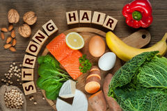 Foods for healthy hair. Healthy hair concept. Best foods for healthy hair as salmon, spinach, almonds, sweet potatoes, eggs, walnuts, cabbage, cheese, red pepper Stock Image