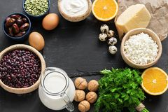 Foods high in calcium on a dark stone background. Healthy eating concept. Dairy products, legumes, greens, eggs and fruits. Top vi stock photo