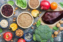 Foods high in iron. liver, broccoli, persimmon, apples, nuts, legumes, spinach, pomegranate. Top view, flat lay. Healthy food with iron content. Vegetables stock image