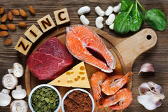 Foods High in Zinc. As salmon, seafood-shrimps, beef, yellow cheese, spinach, mushrooms, cocoa, pumpkin seeds, garlic, bean and almonds. Top view Royalty Free Stock Image