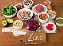 Foods med zinkmineral på en trätabell arkivbild