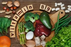 Foods rich in vitamin B9. Folic acid as liver, asparagus, broccoli, eggs, salad, avocado, yeast, nuts, spinach, orange and beans. Top view royalty free stock photo