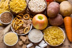 Foods som är höga i kolhydrat på lantlig träbakgrund royaltyfri foto