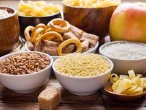 Foods som är höga i kolhydrat på lantlig träbakgrund royaltyfri fotografi