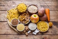 Foods som är höga i kolhydrat på lantlig träbakgrund royaltyfri bild